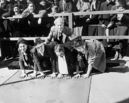 19 Feb 1933, Hollywood, Los Angeles, California, USA --- The four Marx Brothers join Sid Grauman's Hall of Fame in the forecourt of the famous Hollywood Chinese Theater. The four brothers are shown left to right, Harpo, Groucho, Zeppo and Chico as they make their hand impressions in the wet cement with Sid Grauman directing. --- Image by © Bettmann/CORBIS